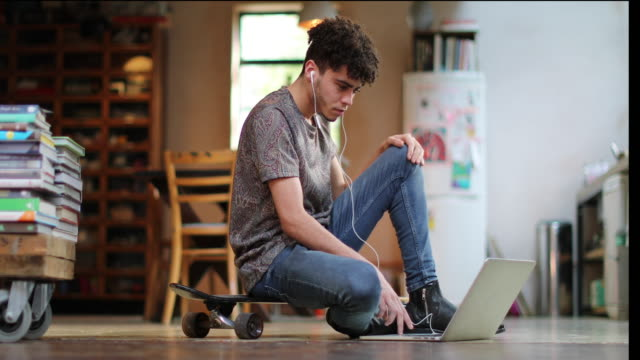 young adult male sitting on skateboard using laptop - cool attitude stock videos & royalty-free footage