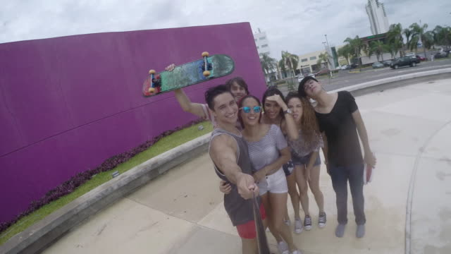Young adult male skateboarder filming self and friends with selfie stick