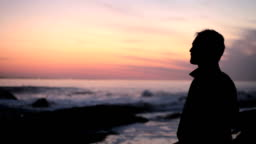 Young adult male staring across the ocean at sunset