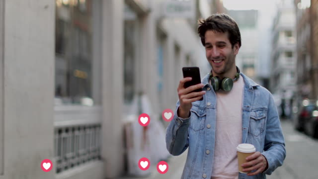 young adult male using smart phone with animation of likes button from social media on city street - social media followers stock videos & royalty-free footage