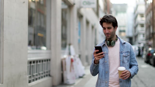 vidéos et rushes de young adult male walking down street looking at smartphone - hipster personne