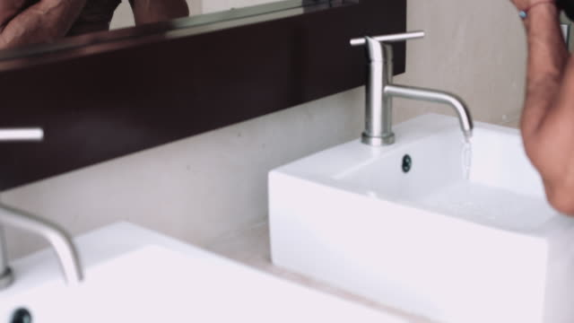 young adult male washing in bathroom sink - one mid adult man only stock videos & royalty-free footage