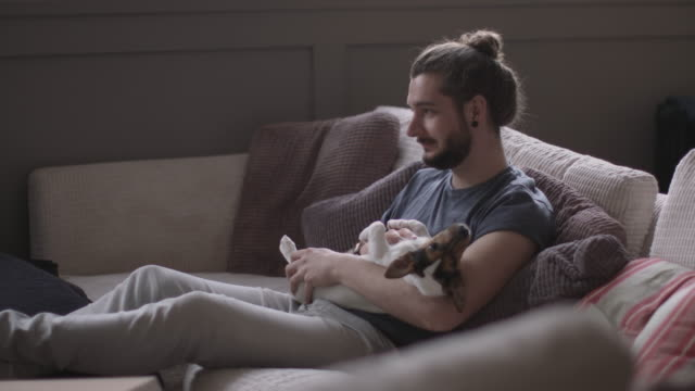 Young adult male watching TV with pet puppy