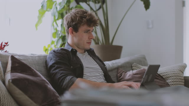 Young adult male working from home in living room