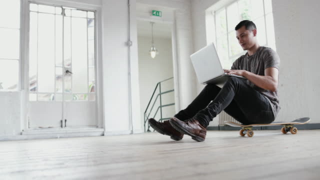 stockvideo's en b-roll-footage met young adult male working on laptop with skateboard - loft apartment
