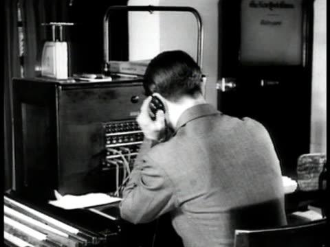 vídeos de stock e filmes b-roll de young adult male working switchboard pulitzer prize winner 'dean of washington newsmen' arthur krock smoking cigar typing at desk in his office - 1935