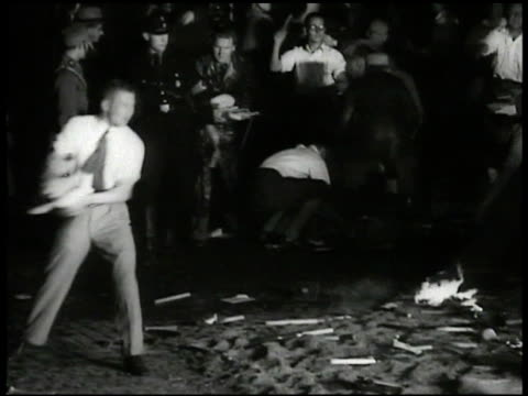 night young adult males german nazi soldiers gathering up books throwing books onto large bonfire people walking behind bonfire sa standing by - judaism stock videos & royalty-free footage