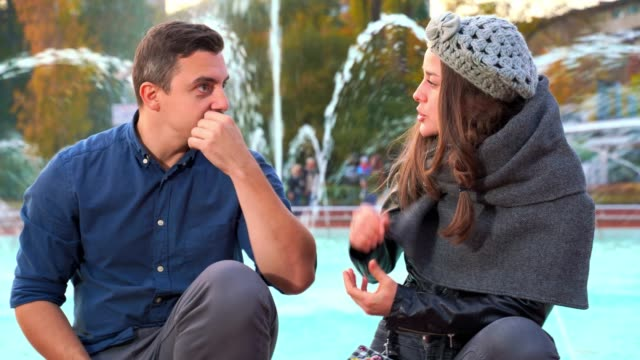Young adult man and woman sitting in front of a beautiful fountain and talking