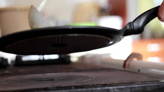 Young Adult Man Baking Pancakes on Furnace in Domestic Kitchen