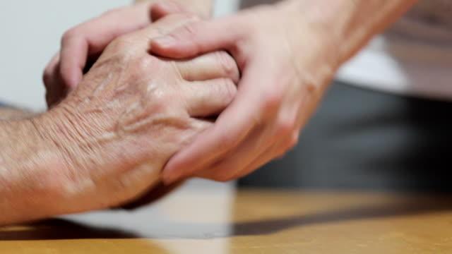 パーキンソン病を持つシニアマンの手を落ち着かせる若い成人男性 - 震える点の映像素材/bロール