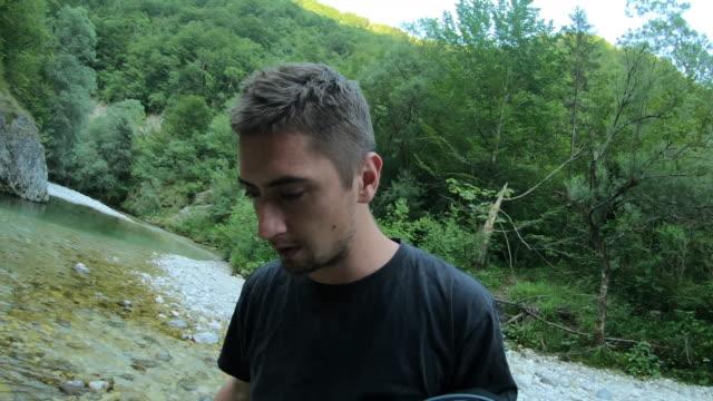 川を渡り、靴を持つ若い大人の男 - 障害物コース点の映像素材/bロール