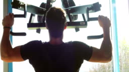 Young Adult Man Doing an Exercise for Arms and Back in Fitness