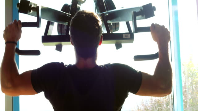 young adult man doing an exercise for arms and back in fitness - exercise machine stock videos & royalty-free footage