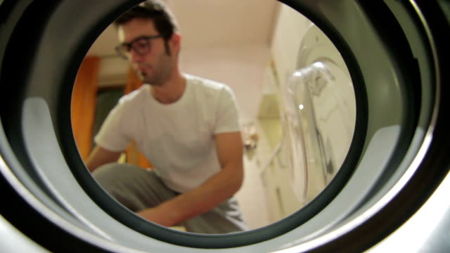 young adult man doing laundry - laundromat stock videos & royalty-free footage