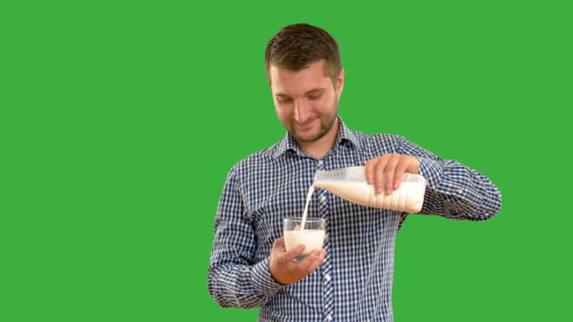 Young adult man drinking milk