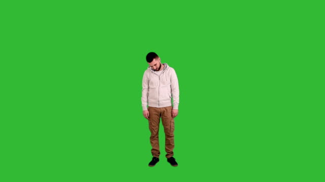 young adult man is sad and going through his head down on green screen background - full length stock videos & royalty-free footage
