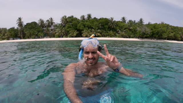 young adult man making a selfie while he's on vacation - snorkeler with scuba mask at maldives - symbols of peace stock videos & royalty-free footage