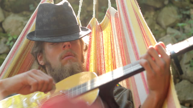 young adult man playing acoustic guitar and relaxing in hammock - hammock stock videos & royalty-free footage