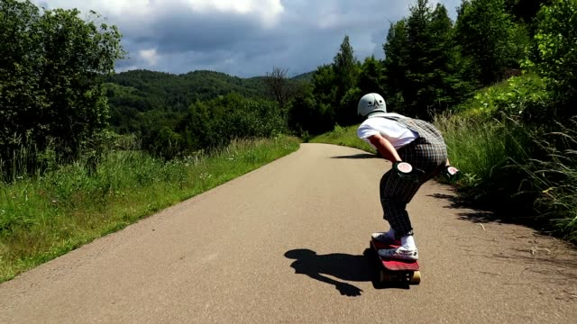 young adult man ridding skateboard downhill - downhill skiing stock videos & royalty-free footage