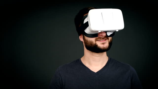young adult  man smiling and using virtual reality glasses