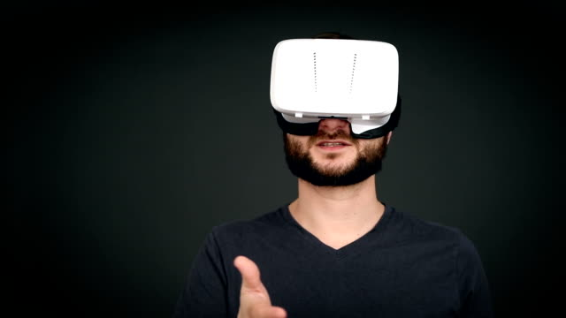 young adult  man speaking and using virtual reality glasses