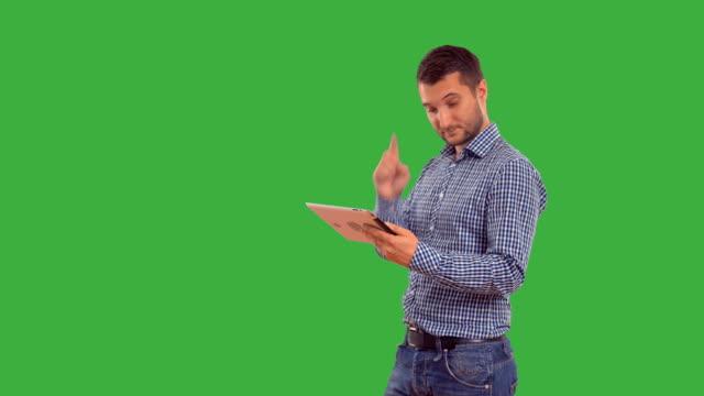 vidéos et rushes de jeune adulte homme parler sur la tablette sur fond vert - objet ou sujet détouré