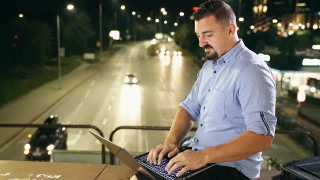 Young adult man using laptop sitting outdoors in front of traffic lights at night