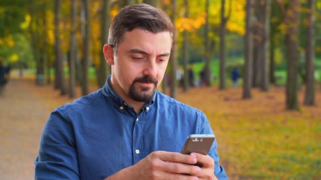 Young adult man using phone outdoors in the city park