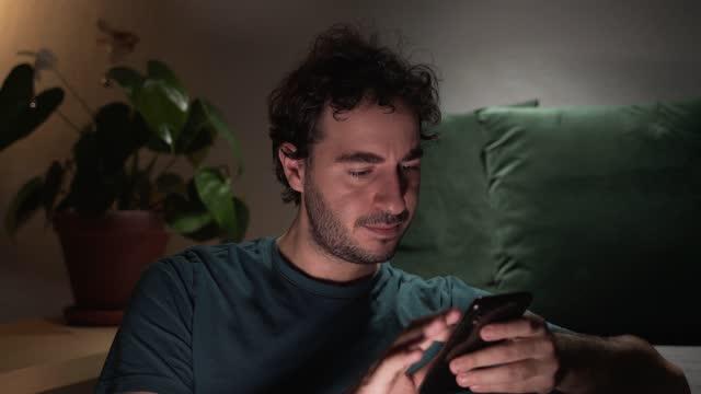 junge erwachsene mann mit smartphone - behaglich stock-videos und b-roll-filmmaterial