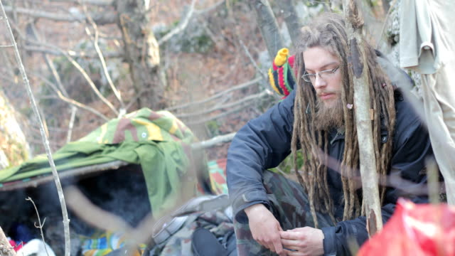 young adult man with dreadlocks camping in nature - homeless shelter stock videos and b-roll footage