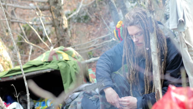 young adult man with dreadlocks camping in nature - survival stock videos & royalty-free footage