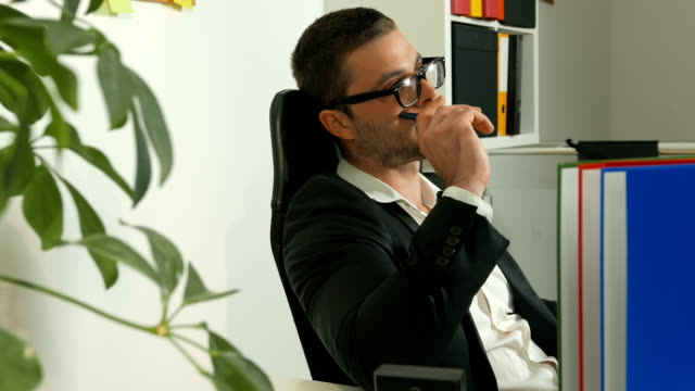 young adult manager is sitting and thinking in the office - reading glasses stock videos & royalty-free footage