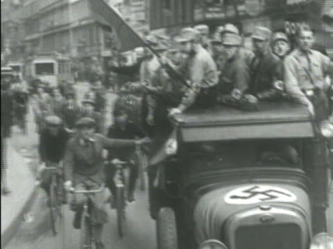 young adult nazi soldiers riding in open truck, holding swastika flags, local german boys on bicycles holding onto moving truck, tram bg. bauhaus... - nazi swastika stock videos & royalty-free footage