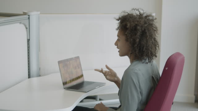 young adult office worker talking on video call with colleagues at desk in office - blouse stock videos & royalty-free footage