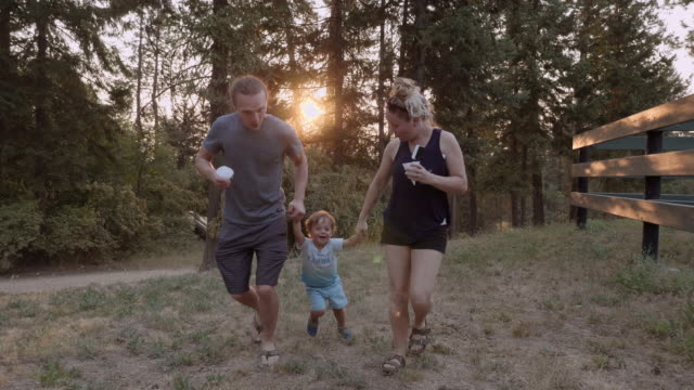 UHD 4K: Young adult parents swinging their laughing child outdoors at sunset