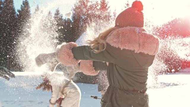 slo mo young adult people having fun in the snow outside on a sunny day - winter video stock e b–roll