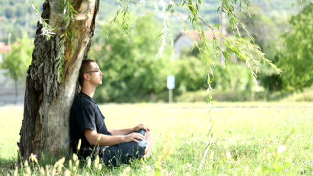 young adult relaxing in public park - zen like stock videos & royalty-free footage