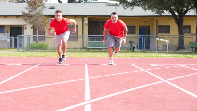 young adult runners at start position on the track field - blocco di partenza per l'atletica video stock e b–roll