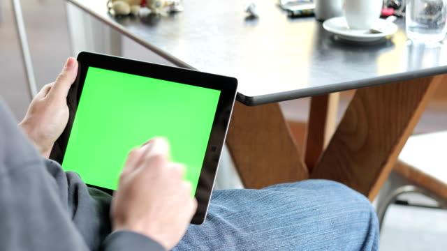 ung vuxen rulla och trycka på på greenscreen på digitala tablett i en bar - över axel perspektiv bildbanksvideor och videomaterial från bakom kulisserna
