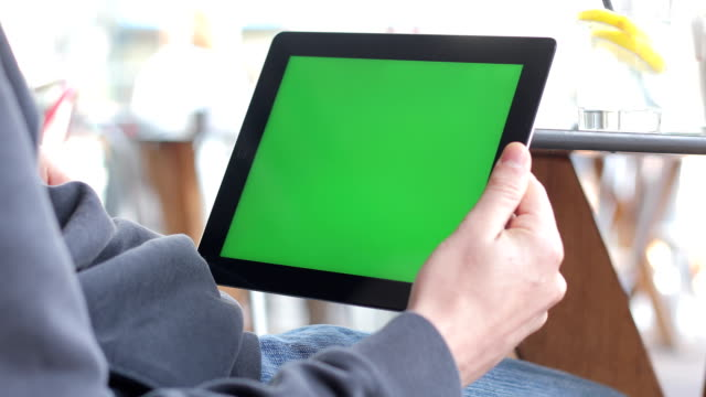 young adult scrolling and tapping on greenscreen on digital tablet - tapping stock videos & royalty-free footage