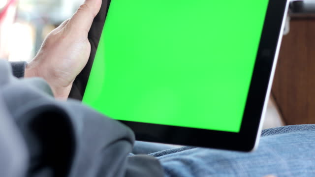 young adult shifting between greenscreens and scrolling on digital tablet - tapping stock videos & royalty-free footage
