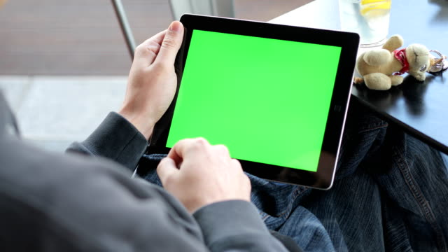 young adult shifting between greenscreens and tapping on digital tablet - tapping stock videos & royalty-free footage