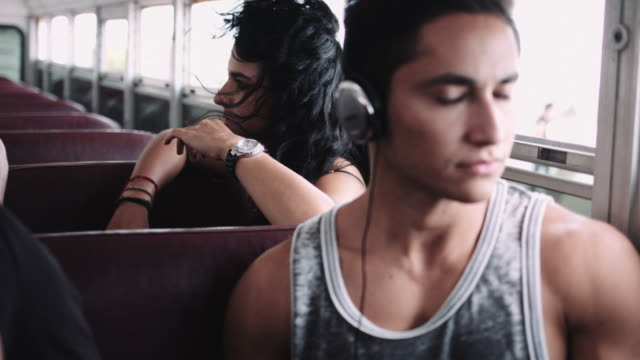 Young adult sitting in bus listening to music on headphone