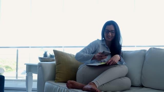 junge erwachsene sitzen auf der couch studing - nur junge frauen stock-videos und b-roll-filmmaterial