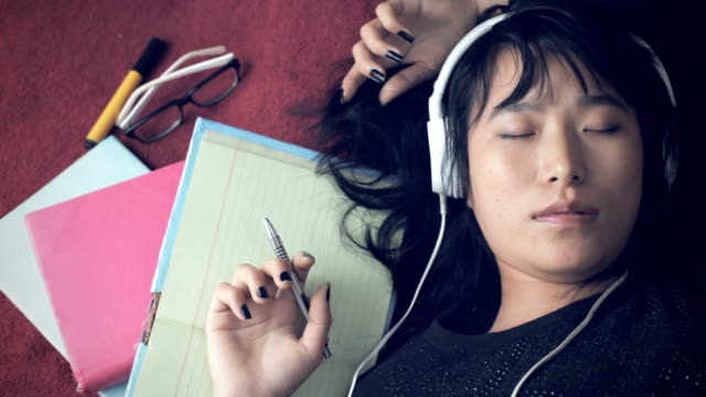 young adult student listening music reclining on carpet. - sleeping stock videos and b-roll footage