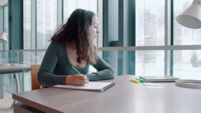 young adult student near window with book - studentessa di scuola secondaria video stock e b–roll