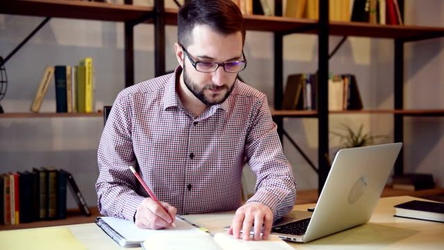 giovane studente con computer portatile e taccuino di carta - archivista video stock e b–roll