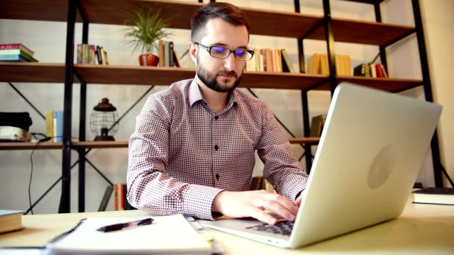 vídeos de stock e filmes b-roll de jovem adulto estudante trabalhando no computador portátil - óculos