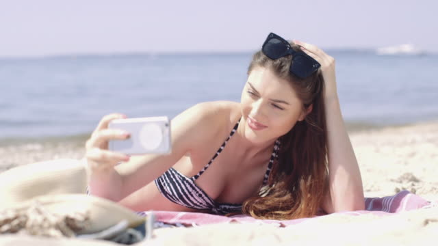 Young adult taking selfie on beach vacation