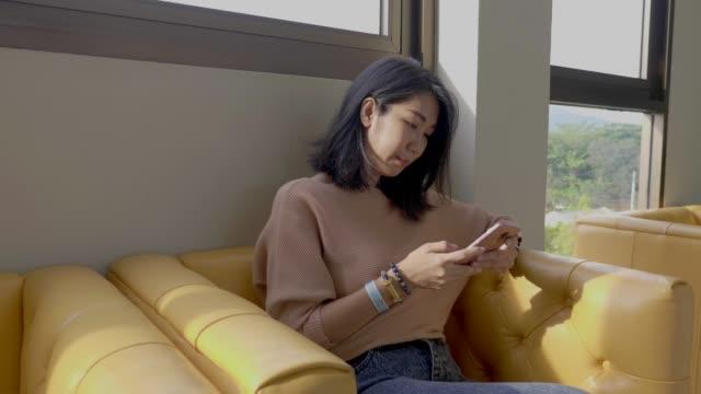 自宅でスマートフォンで話す若い大人。 - 下を向く点の映像素材/bロール